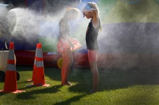 Briana Sanchez | Tribune Laura and Aleea Miedema play with the water misting fans at Rockin' Robbins Tuesday evening.