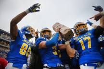 South Dakota State University's Adam Anderson, from left, Joshua Manchigiah and Alex Romenesko hold the Dakota Marker up to the student section after their win over North Dakota State University Saturday, Nov. 4, at Dana Dykhouse Stadium in Brookings.