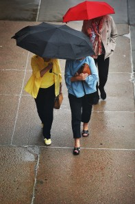 Pedestrians make their way through downtown Wednesday, June 20, while the rain comes down. Chance of precipitation for today was 100%. New rainfall amounts between three quarters and one inch possible.