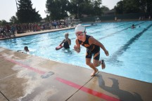 Evelyn DeGeest finishes her lap and runs to the bikes during the Parks and Recreation Youth Triathlon at Kuehn Park Friday, Aug 10, in Sioux Falls.