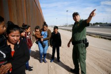 Border patrol agent Joe Romero directs a group of women and children from Ecuador to another agent for transport Tuesday, Feb. 18, by the east bridge near Staton bride in El Paso. The women turned themselves in with their children.