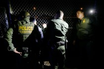 Border patrol agents apprehend two Ecuadorian migrants at the border fence near Cesar E. Chavez Border Highway Tuesday, Feb. 18, in El Paso.